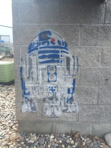 Graffiti of R2D2, is shown facing the sidewalk outside of Nauvoo House apartment complex. (Lauren Conte, Scroll Photography)
