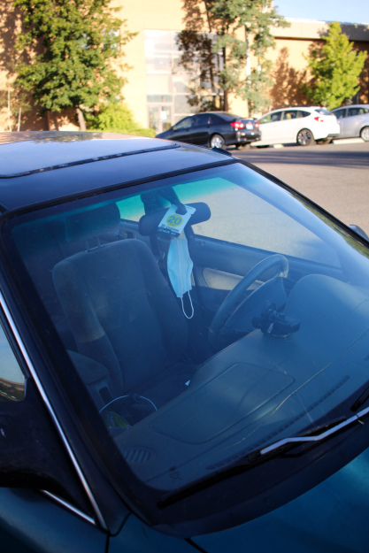 Photo courtesy of Carrin Nelson, photo of a mask hanging from the rearview mirror of a car