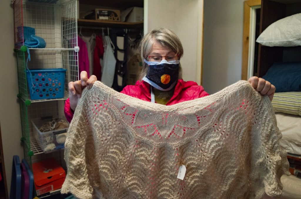 Freeman holds a shawl she knit herself years ago — creating these takes the longest out of anything she makes.