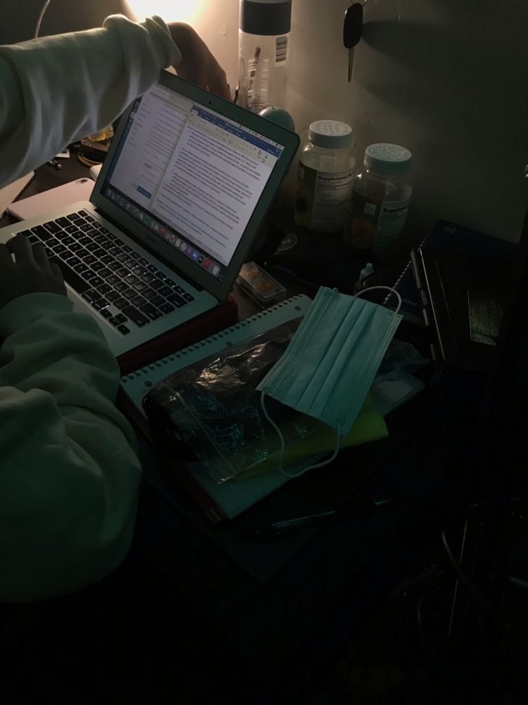 Photo courtesy of Eliza Kent, photo of a student studying at a desk with a mask close by