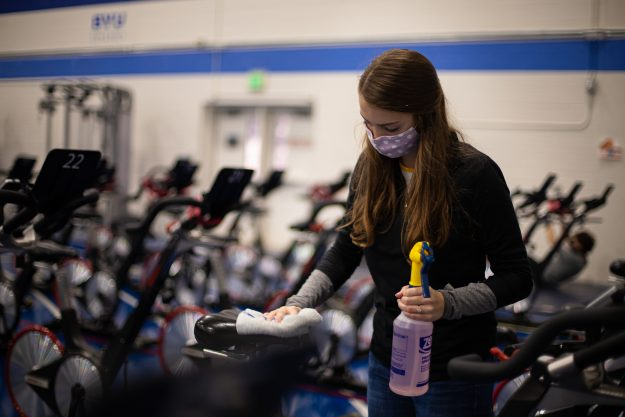 Photo courtesy of Emily Russell, photo of a BYU-Idaho employee wiping down cycling equipment