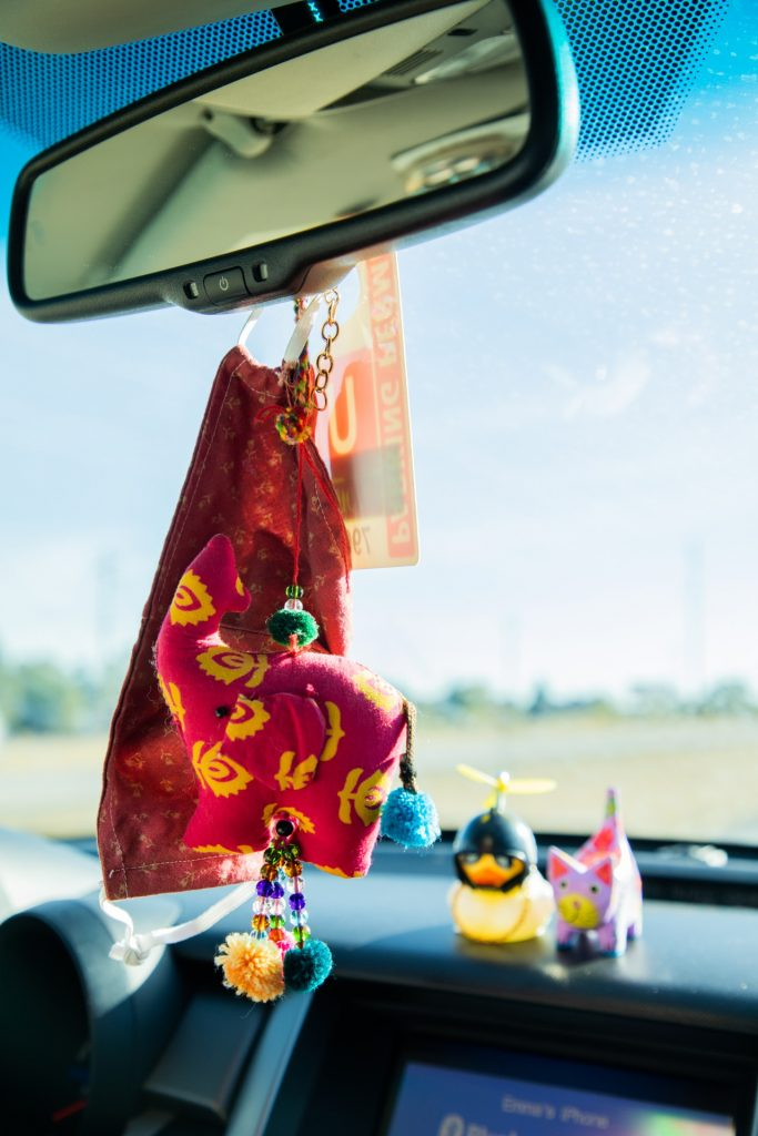 photo of a homemade mask hanging from the review mirror of a car