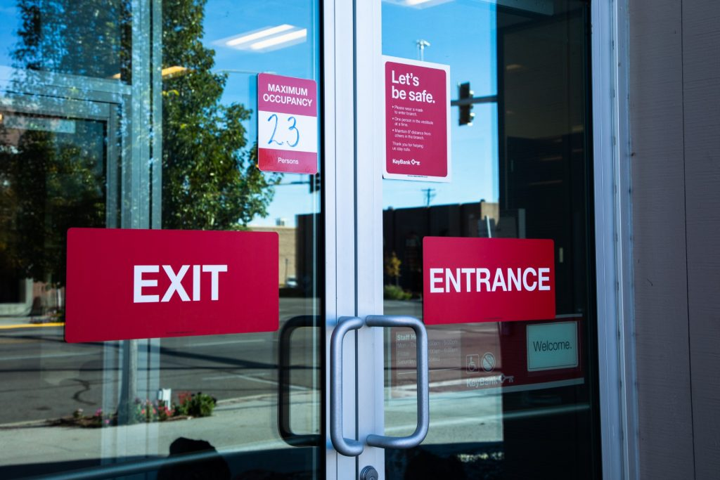 A photo of an exit and entrance sign on a business door