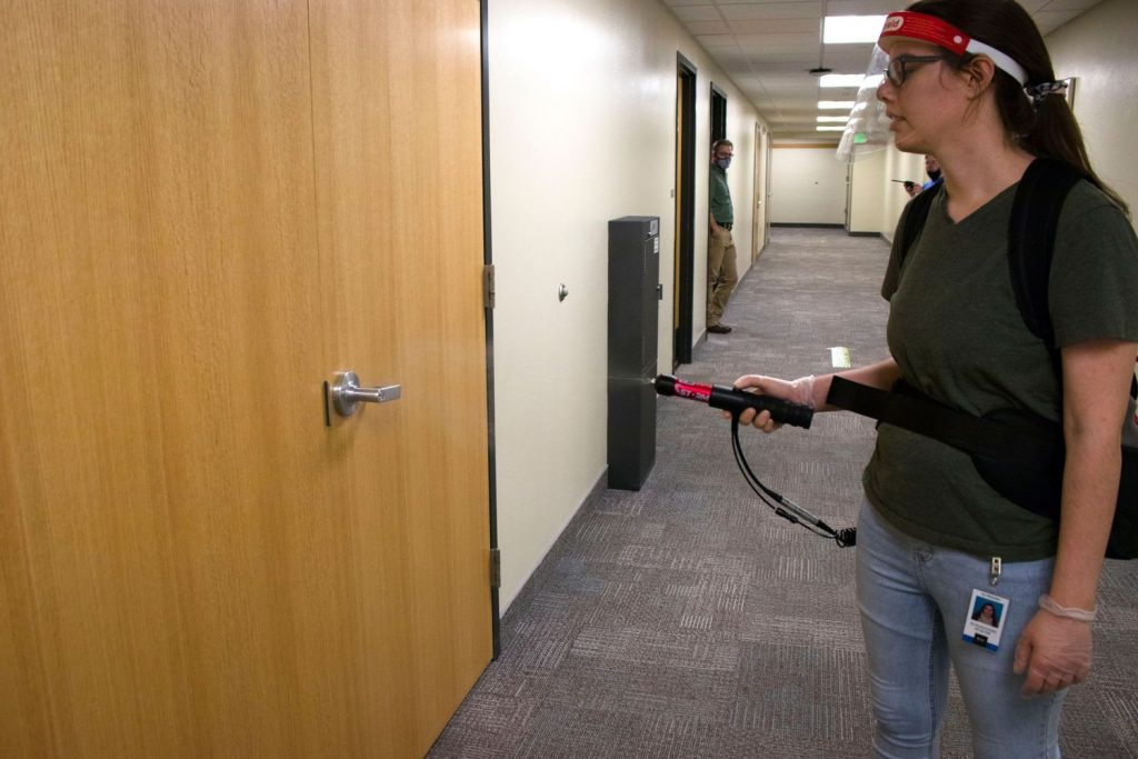 Photo courtesy of Megan White, photo of a BYU-Idaho employee spraying the door handle in the MC