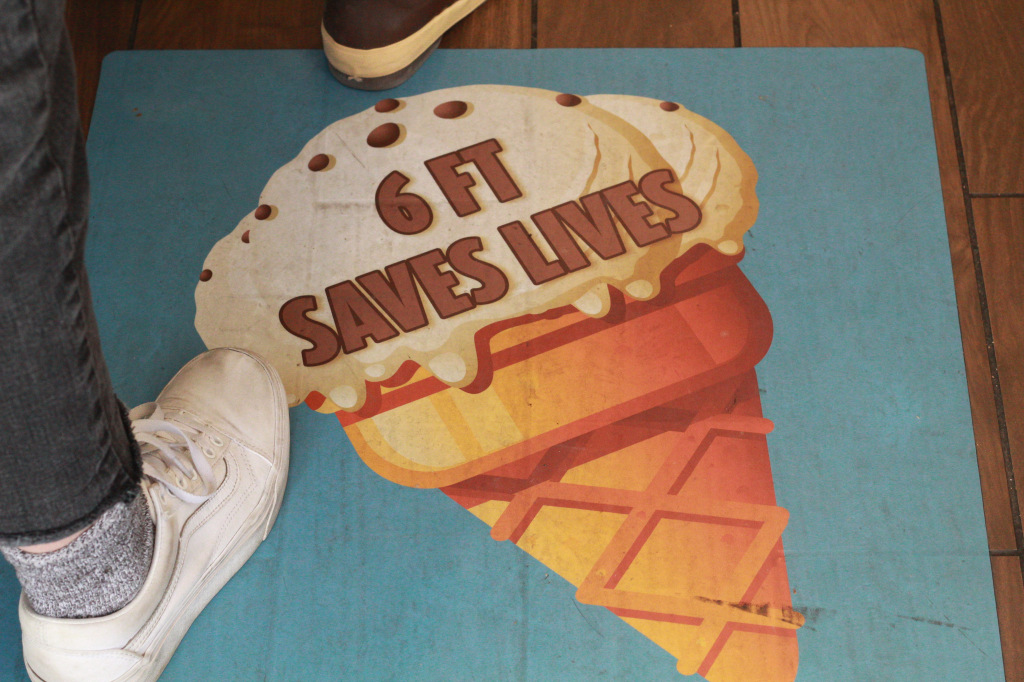 """Photo courtesy of Olivia Weaver, photo of a sign on the ground of an ice cream parlor reads """"6 FT SAVES LIVES"""""""