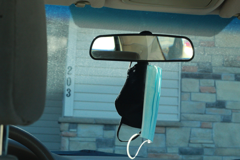 Photo courtesy of Olivia Weaver, photo of masks hanging from the rearview mirror of a car