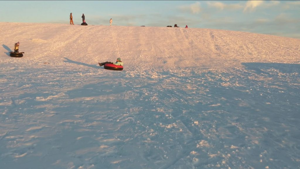 People enjoying going down the snow-covered hills at the St. Anthony Sand Dunes